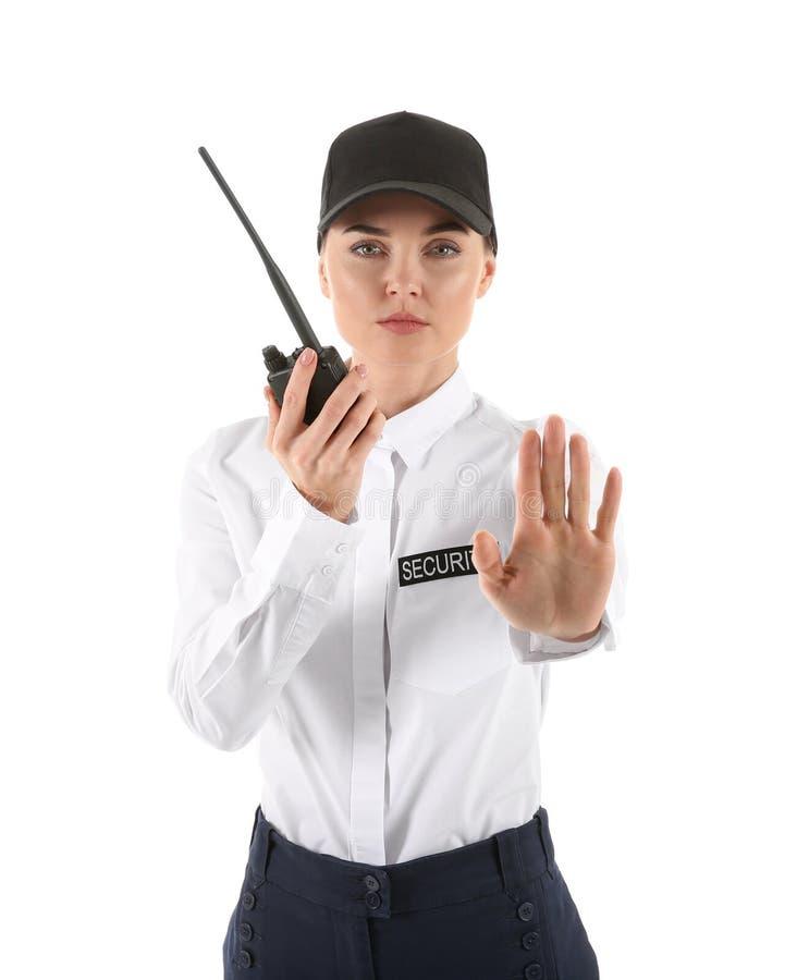 Guardia de seguridad femenino con gesto de la parada de la demostración del transmisor de la radio portátil en el fondo blanco foto de archivo libre de regalías