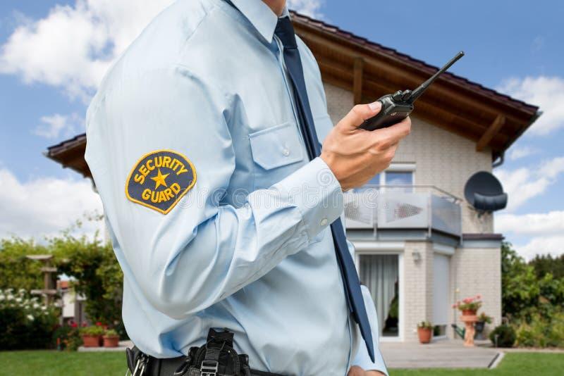 Guardia de seguridad Holding Walkie Talkie foto de archivo libre de regalías