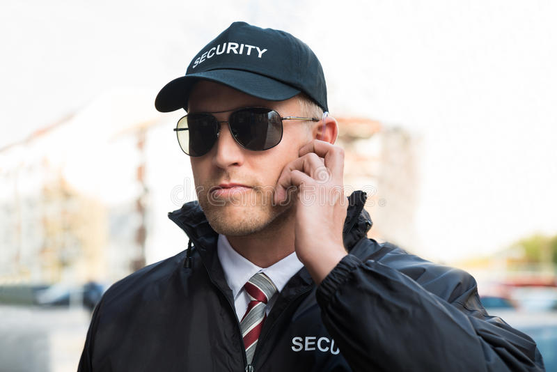 Guardia de seguridad Listening To Earpiece fotos de archivo