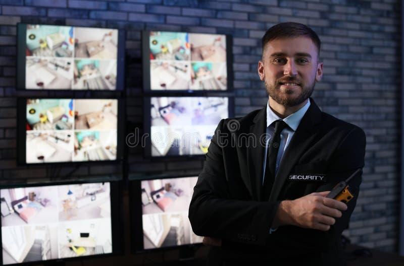 Guardia de seguridad masculino con el transmisor portátil cerca de cámaras fotografía de archivo libre de regalías