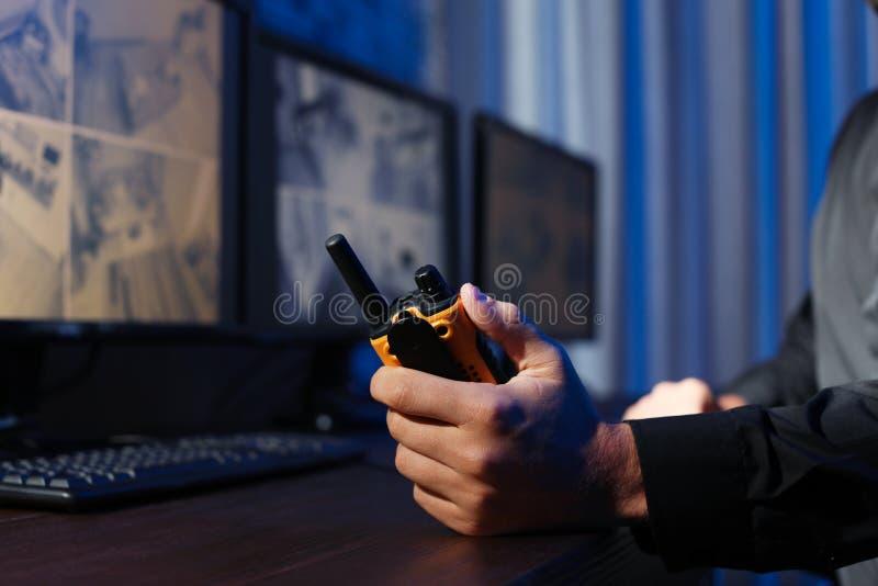 Guardia de seguridad masculino con el transmisor portátil que supervisa las cámaras CCTV modernas dentro imagen de archivo libre de regalías