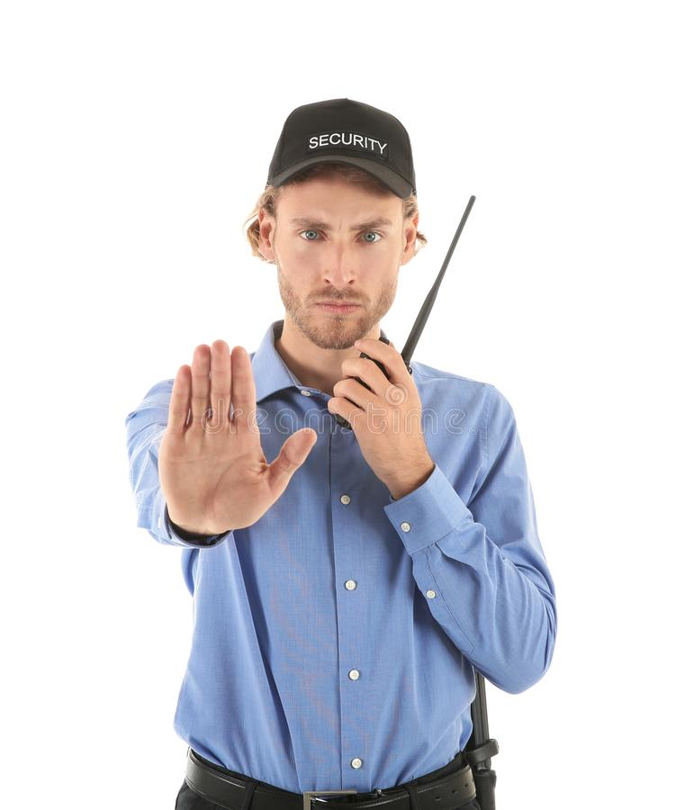 Guardia de seguridad masculino con gesto de la parada de la demostración del transmisor de la radio portátil en el fondo blanco fotografía de archivo