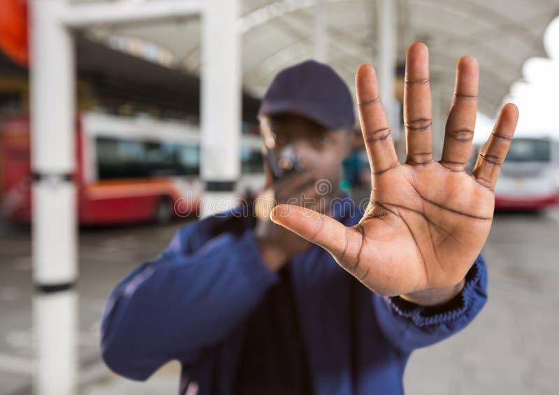guardia de seguridad que dice la parada con su mano en el término de autobuses imágenes de archivo libres de regalías