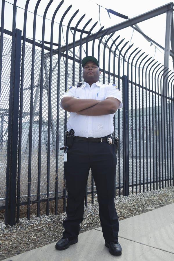 Guardia de seguridad Standing In Front Of Prison Fence fotografía de archivo
