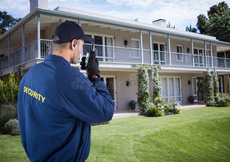 Guardia de seguridad usando radio fuera de la casa fotos de archivo libres de regalías