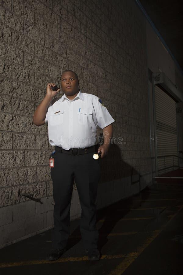 Guardia de seguridad Using Walkie Talkie mientras que patrulla en la noche imágenes de archivo libres de regalías