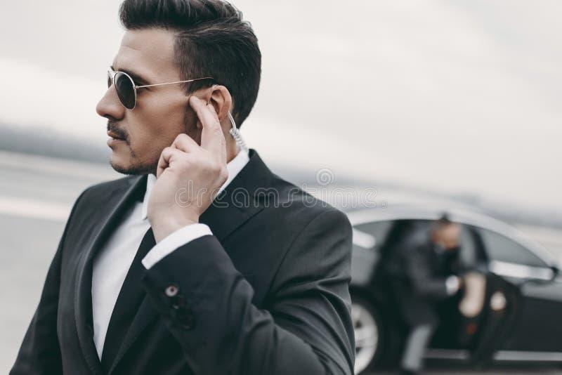 guardia del corpo bella del messaggio d'ascolto dell'uomo d'affari fotografia stock