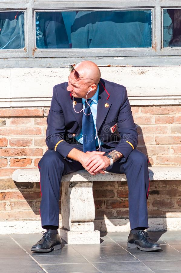 Guardia del museo che si siede su un banco di pietra nel giardino dei musei del Vaticano e che guarda sui turisti di camminata immagini stock libere da diritti