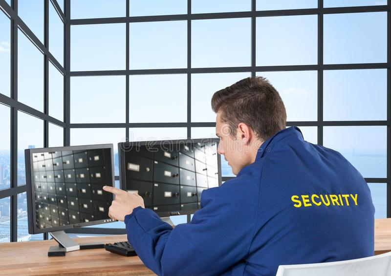 guardia giurata che guarda l'immagine dello ione della videocamera di sicurezza gli schermi nel suo ufficio fotografia stock