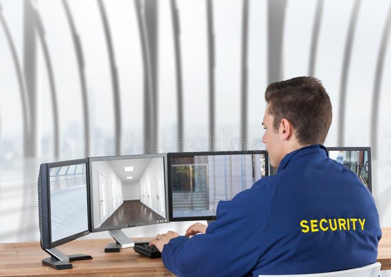 guardia giurata che guarda le immagini delle videocamere di sicurezza sugli schermi, nell'ufficio fotografia stock