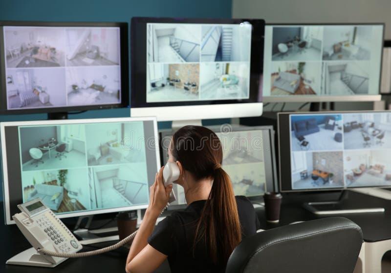 Guardia giurata che parla dal telefono mentre controllando le macchine fotografiche moderne del CCTV nella stanza di sorveglianza fotografia stock