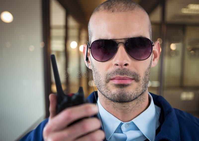 guardia giurata con i vetri, la cuffia ed il walkie-talkie nell'ufficio fotografie stock libere da diritti