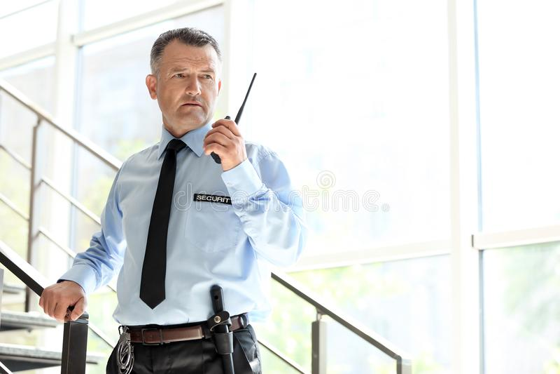 Guardia giurata maschio facendo uso della radiotrasmittente portatile fotografia stock