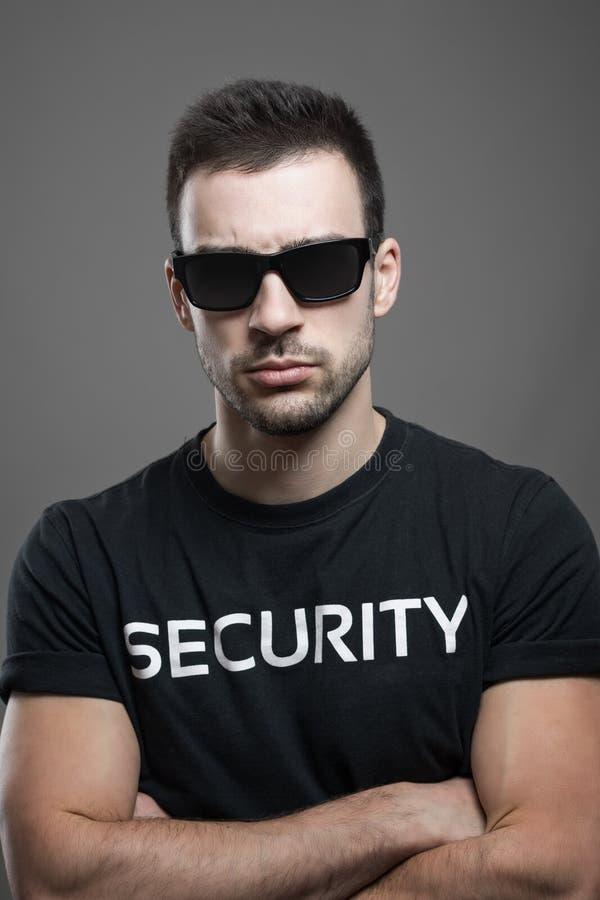 Guardia giurata maschio seria macho dura con gli occhiali da sole e le armi attraversate che esaminano macchina fotografica immagini stock libere da diritti