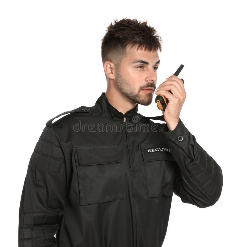 Guardia giurata maschio in uniforme facendo uso della radiotrasmittente su fondo bianco fotografie stock libere da diritti