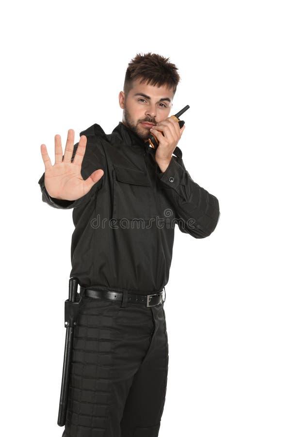 Guardia giurata maschio in uniforme facendo uso della radiotrasmittente su fondo bianco immagini stock libere da diritti
