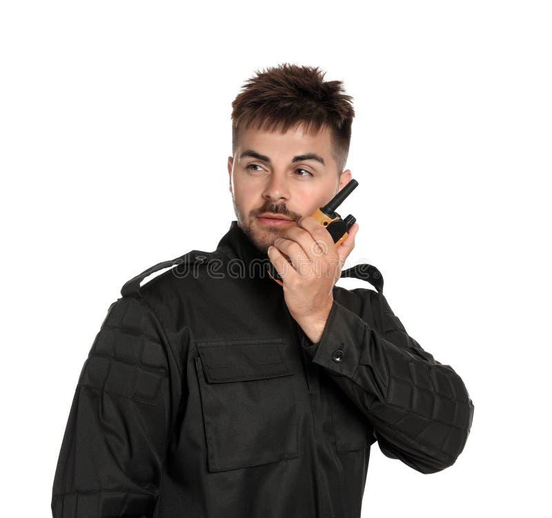 Guardia giurata maschio in uniforme facendo uso della radiotrasmittente su fondo bianco fotografia stock libera da diritti