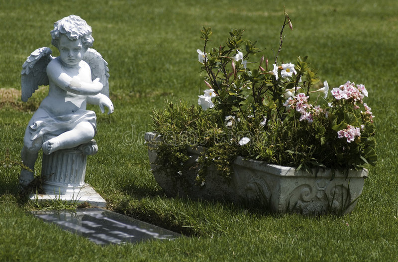 Guardian Angel. Angelic statue and bouquet of flowers adorn the headstone of a deceased love one royalty free stock image