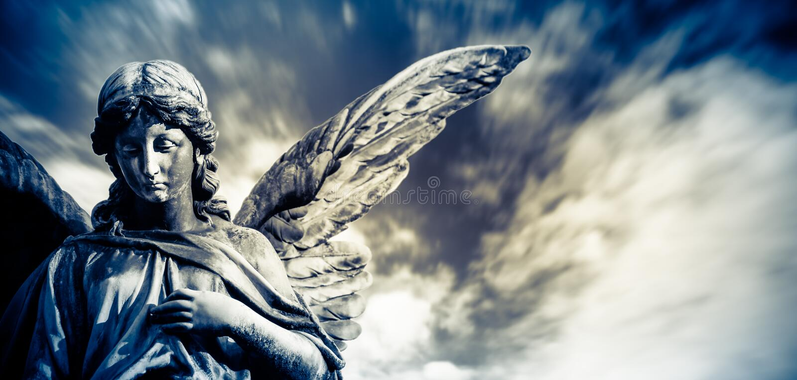 Guardian angel sculpture with open long wings  with blurred white clouds dramatic light blue sky. Angel sad expression stock image