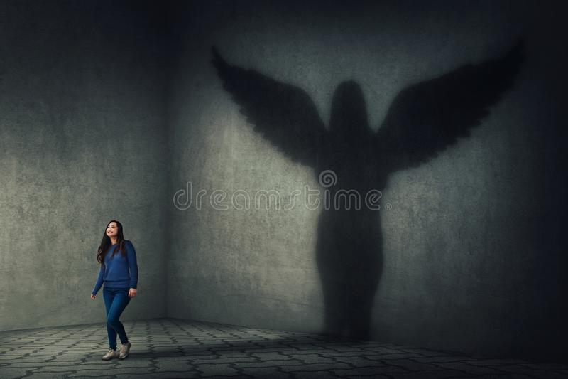 Guardian angel shadow. Proud and confident young woman walking and casting a superhero shadow as a guardian angel with wings on a dark room wall. Inner power stock image