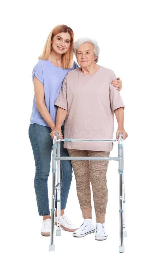 Guardiano che aiuta donna anziana con la struttura di camminata su bianco immagine stock libera da diritti
