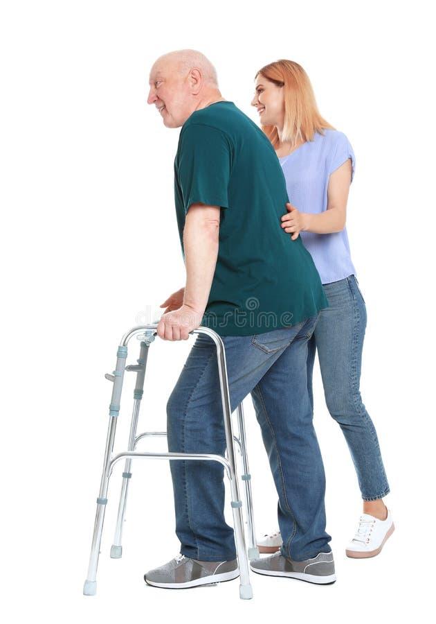 Guardiano che aiuta uomo anziano con la struttura di camminata su bianco fotografia stock libera da diritti