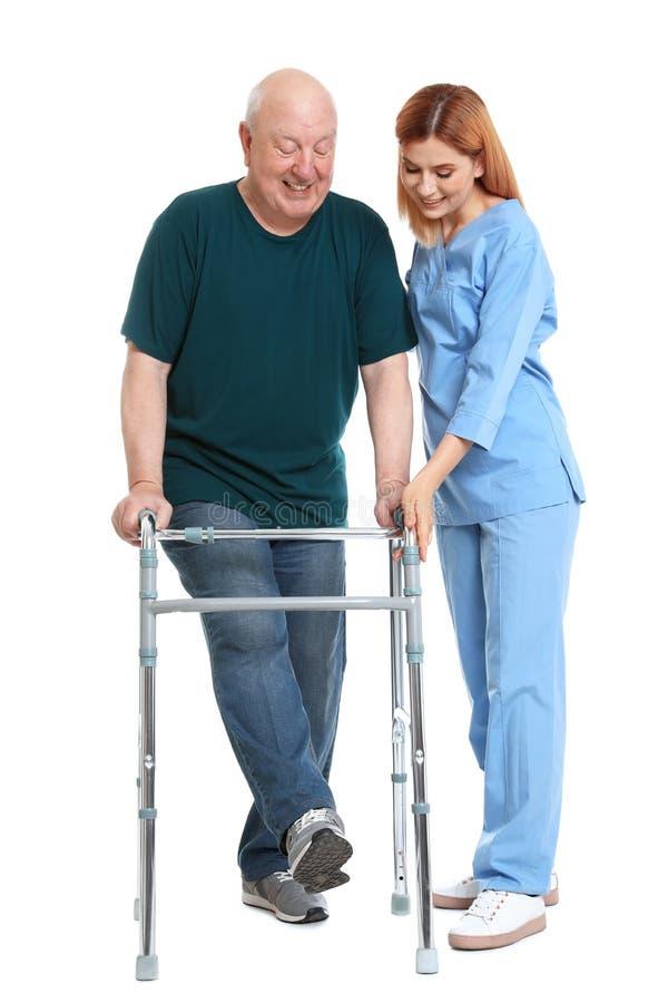 Guardiano che aiuta uomo anziano con la struttura di camminata su bianco immagini stock