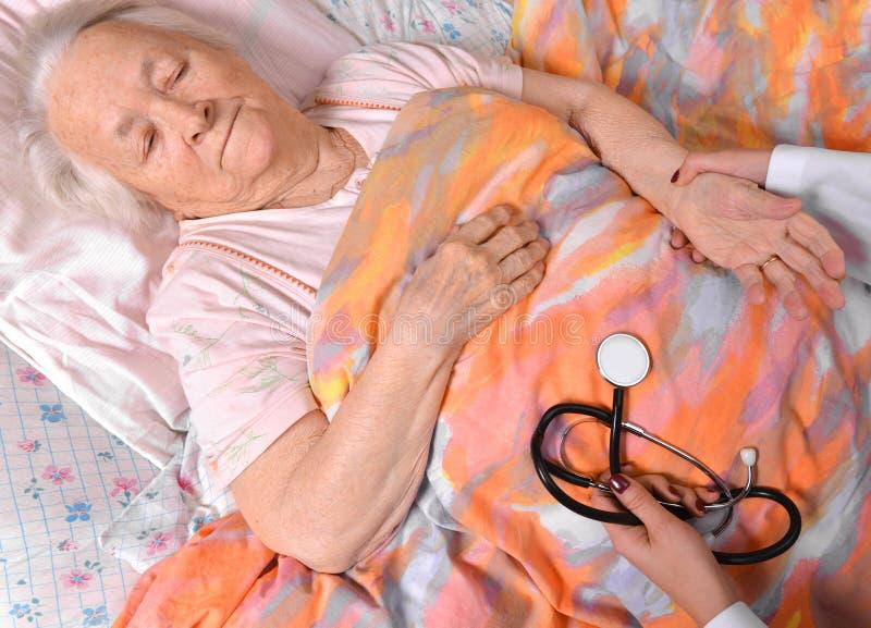 Guardiano femminile che controlla impulso della donna anziana fotografia stock