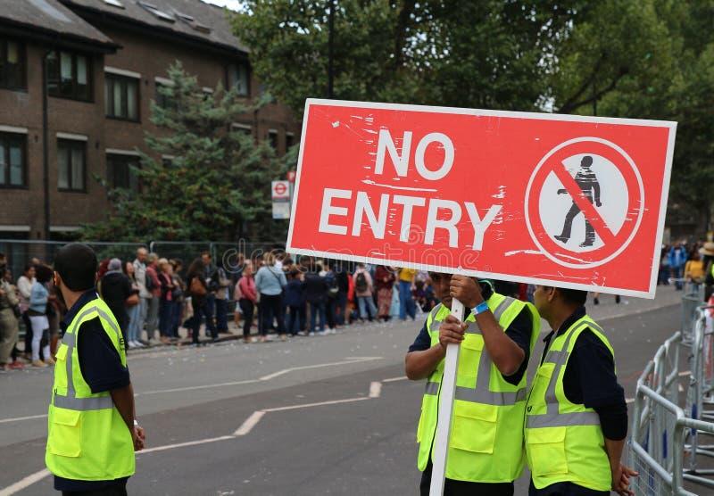 Guardias de seguridad del carnaval de Notting Hill con la muestra prohibida del paso imágenes de archivo libres de regalías
