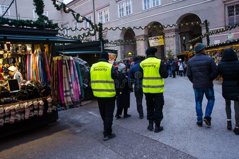 Guardias de seguridad que caminan en mercado de la Navidad foto de archivo