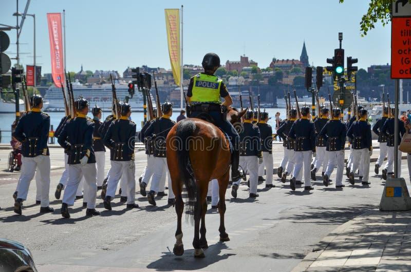 Guardias reales con la escolta policial en Estocolmo, Suecia imagen de archivo