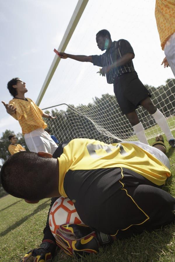 Guardien de but avec la bille de football, arbitre à l'arrière-plan photo libre de droits