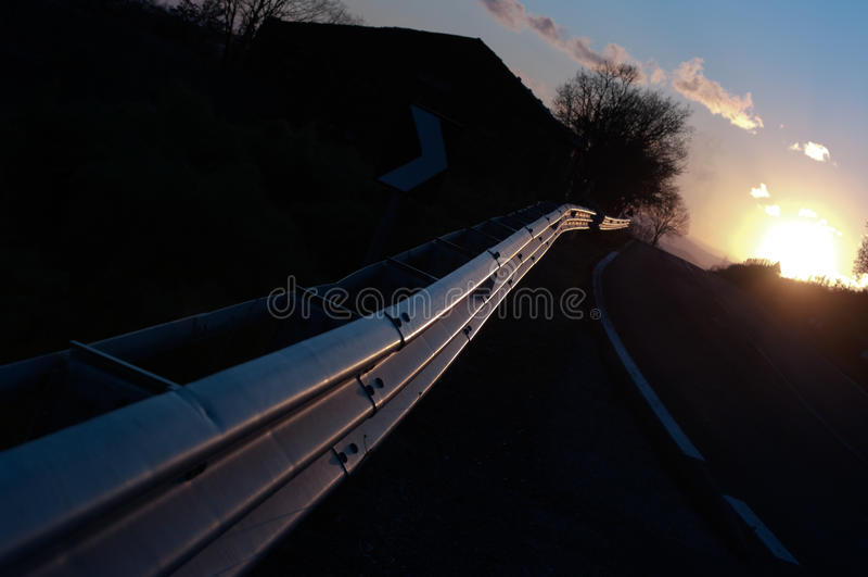 Guardrail Vanish On Road At Sunset. The light of sunset is refletting by vanish guardrail at horizon stock image