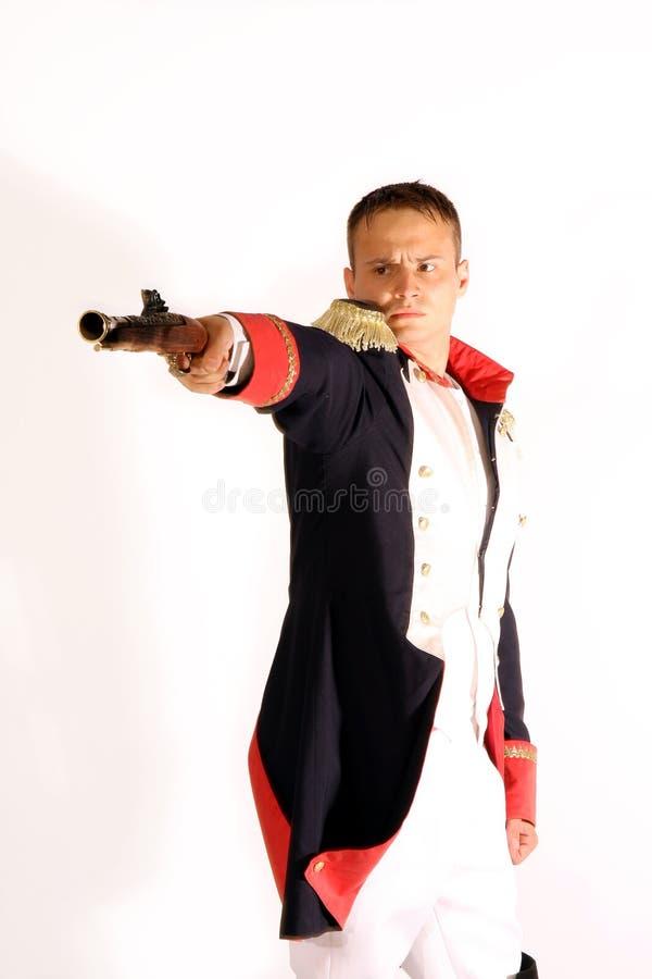 Guardsman in full-dress uniform aiming gun. Guardsman in full-dress uniform of the Russian army of times Ekaterina II aiming gun, isolated on white royalty free stock image