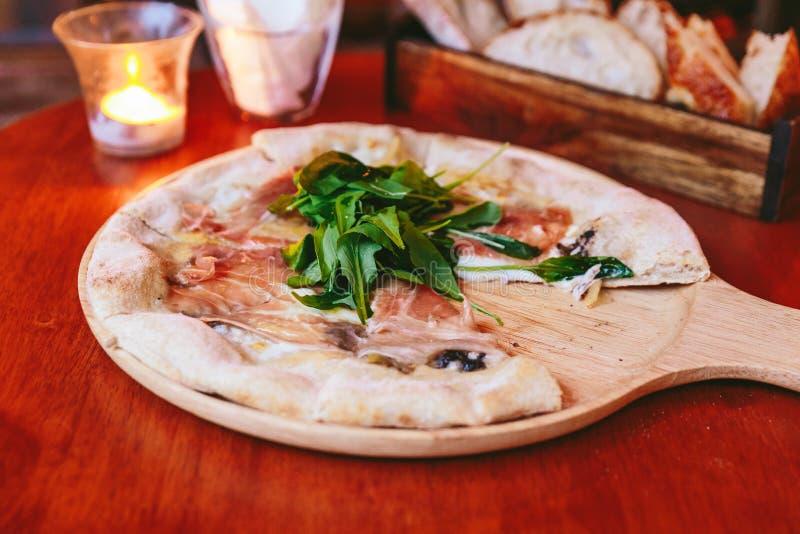 Guarnizione di Parma Ham Pizza con il razzo sul piatto di legno arrotondato con le fette mancanti e sul pane affettato in scatola fotografia stock