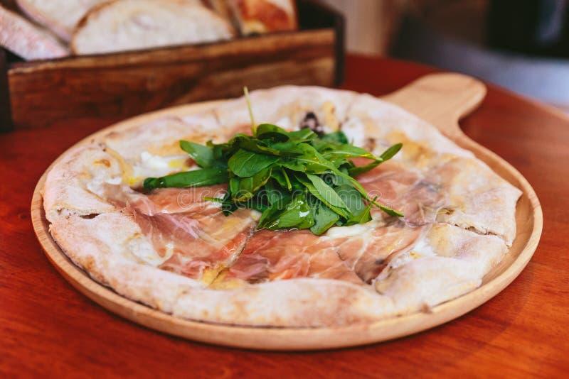 Guarnizione di Parma Ham Pizza con il razzo sul piatto di legno arrotondato con pane affettato in scatola di legno nei precedenti fotografia stock