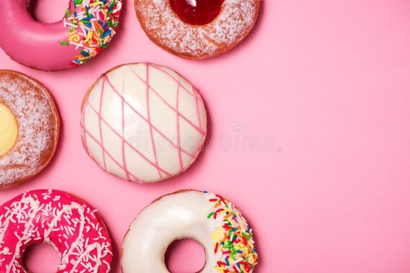 Guarnizioni di gomma piuma con glassa sul fondo di rosa pastello Guarnizioni di gomma piuma dolci immagine stock