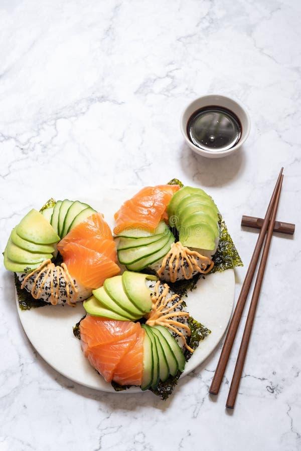 Guarnizioni di gomma piuma dei sushi con l'avocado ed il cetriolo di color salmone immagini stock