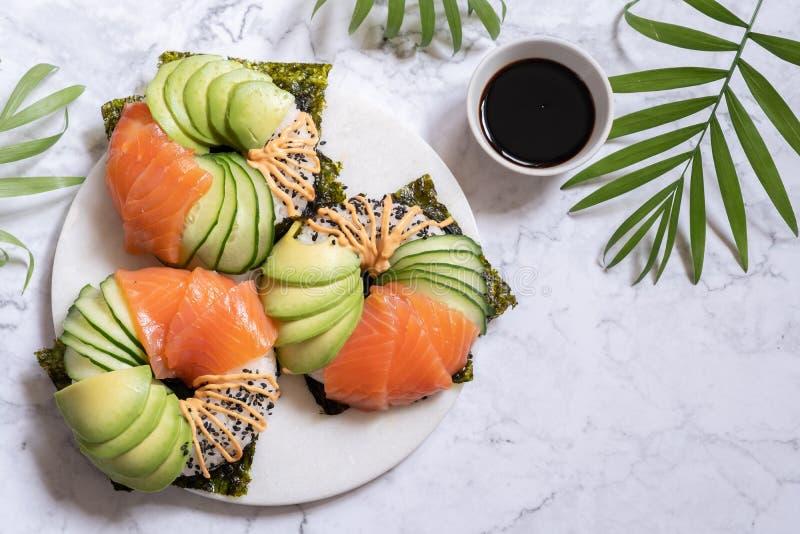 Guarnizioni di gomma piuma dei sushi con l'avocado ed il cetriolo di color salmone fotografie stock