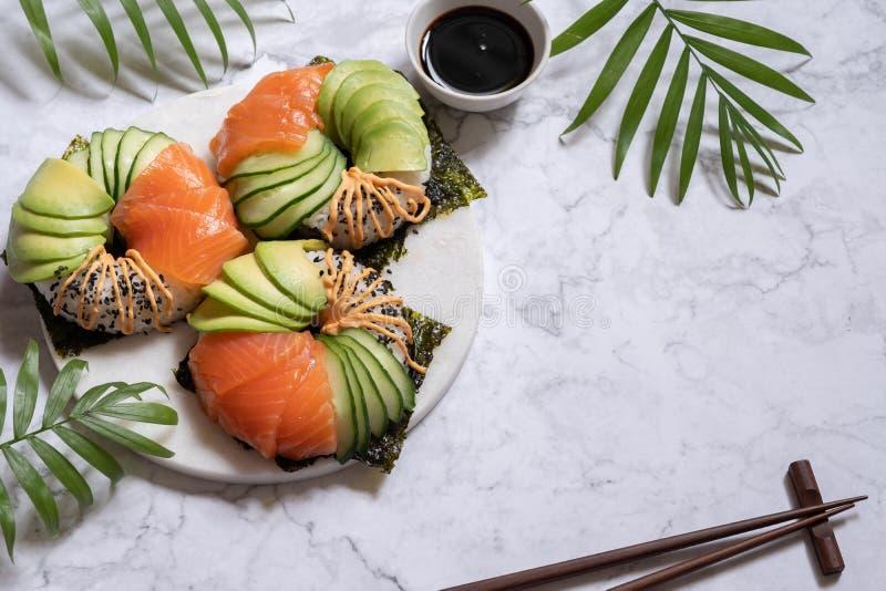 Guarnizioni di gomma piuma dei sushi con l'avocado ed il cetriolo di color salmone immagine stock libera da diritti