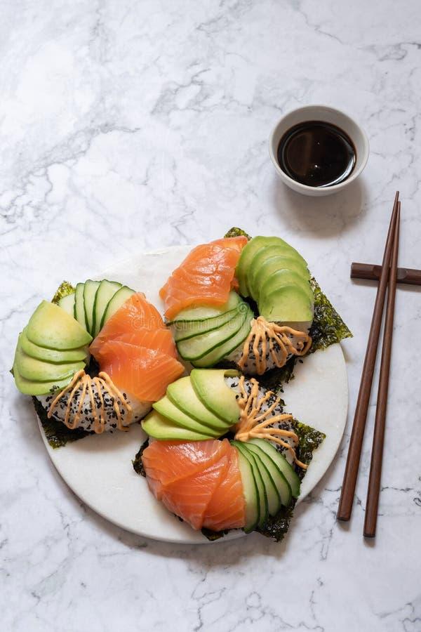 Guarnizioni di gomma piuma dei sushi con l'avocado ed il cetriolo di color salmone immagine stock