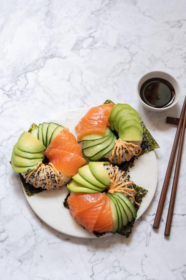 Guarnizioni di gomma piuma dei sushi con l'avocado ed il cetriolo di color salmone fotografia stock