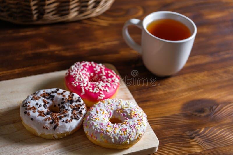 Guarnizioni di gomma piuma e tazza lustrate di tè su fondo di legno e sul canestro vicino del rattan fotografie stock libere da diritti