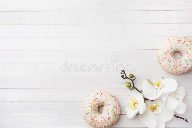 Guarnizioni di gomma piuma ed orchidea bianca sulla tavola bianca con lo spazio della copia Disposizione piana, vista superiore immagine stock libera da diritti