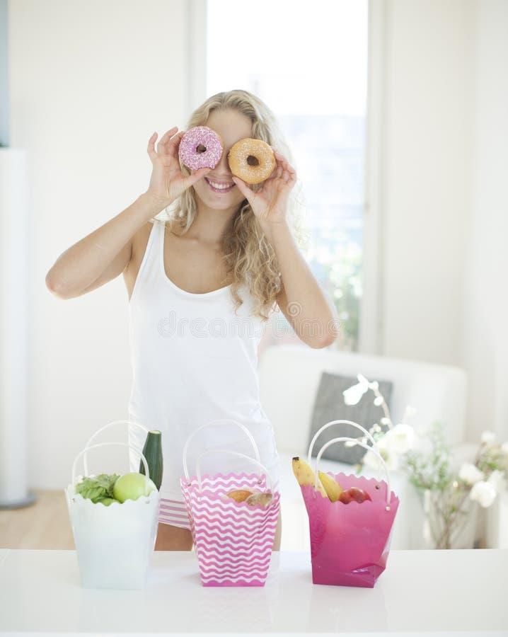 Guarnizioni di gomma piuma felici della tenuta della donna davanti agli occhi al contatore di cucina immagine stock