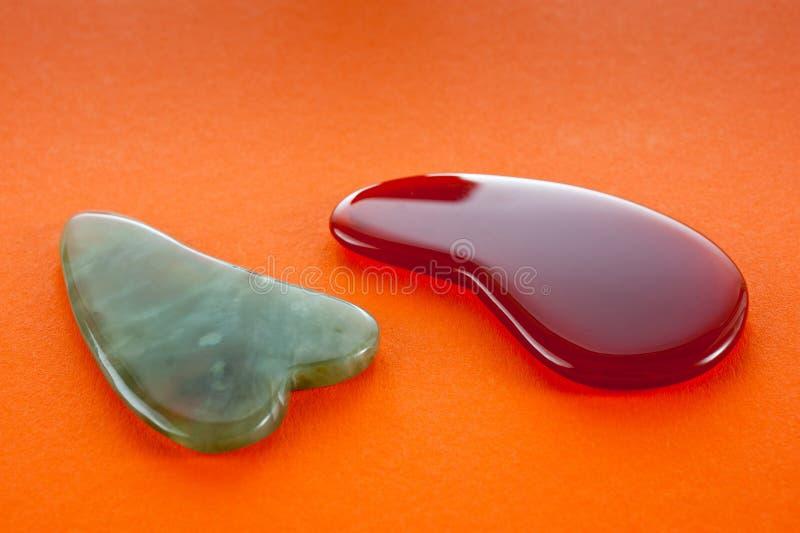Guasha-Schaber für Körpermassage entsprechend der alten Methode schossen auf einem hellen roten Hintergrund lizenzfreies stockfoto