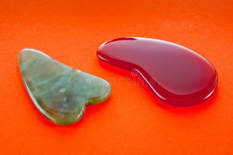 Guasha-Schaber für Körpermassage entsprechend der alten Methode schossen auf einem hellen roten Hintergrund lizenzfreies stockbild