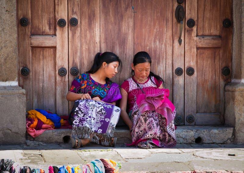 Guatamalian girls salling traditional colorful fabric and good royalty free stock photo