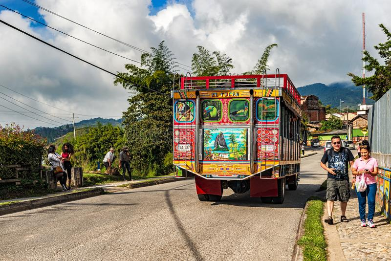 Colorful public bus on the road in Guatape, Colombia. Guatape, Colombia – March 27, 2018: Colorful old public bus on the road in Guatape, Colombia royalty free stock photo