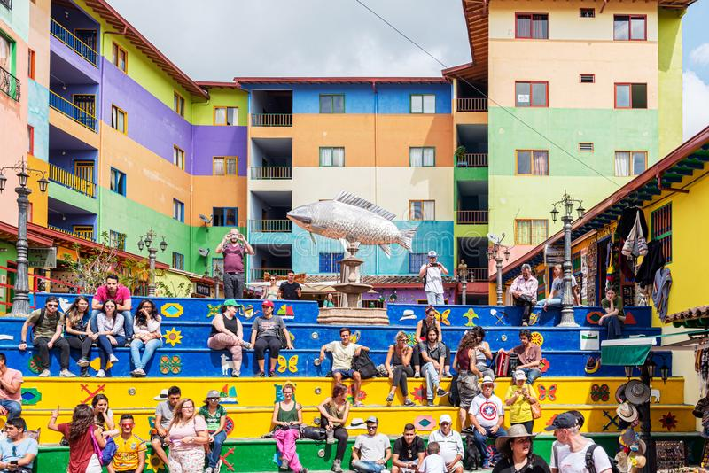 Plaza de Zocalos a popular place to visit in Guatape near Medellin in Colombia. Guatape, Colombia – March 27, 2019: Tourists are sitting on the colourful royalty free stock photo